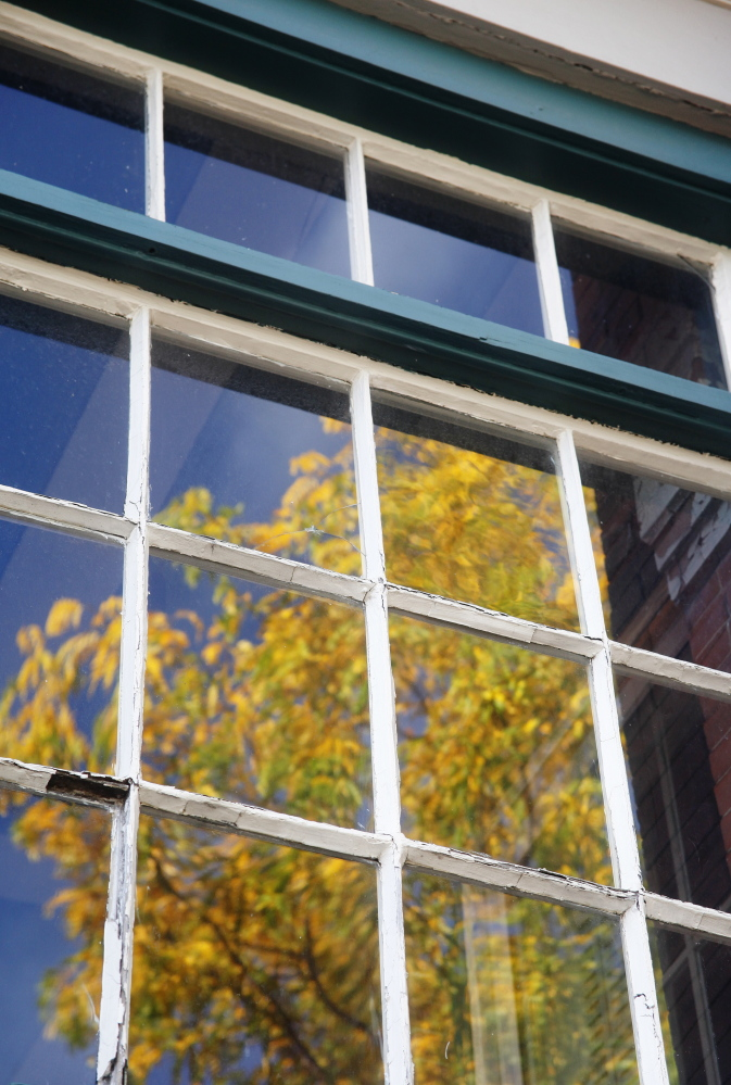 Antique windows reflect foliage at 147 Congress St. on Munjoy Hill in Portland where the owners are asking to make it a historic landmark to protect it from ruin after it sells.