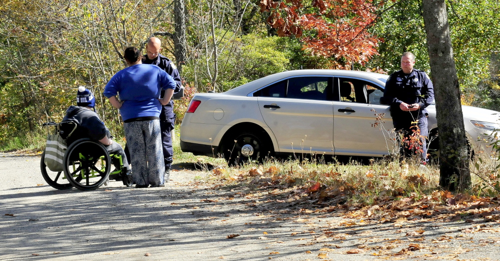 Two Maine State Police investigators interview people outside 354 Rutland Road in Plymouth near where the body of a person was found on the road Monday morning.