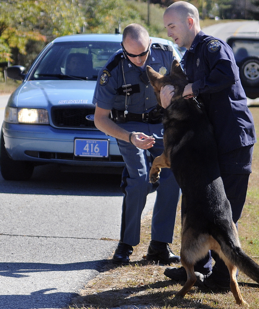 Maine State Trooper Eric Verhille, right, restrains his dog Monday as Trooper Chris Rogers collects evidence following the arrest of Scott Howard in South Gardiner. Howard was charged with a number of counts after allegedly threatening to burn down his former girlfriend's home and kill her dog.