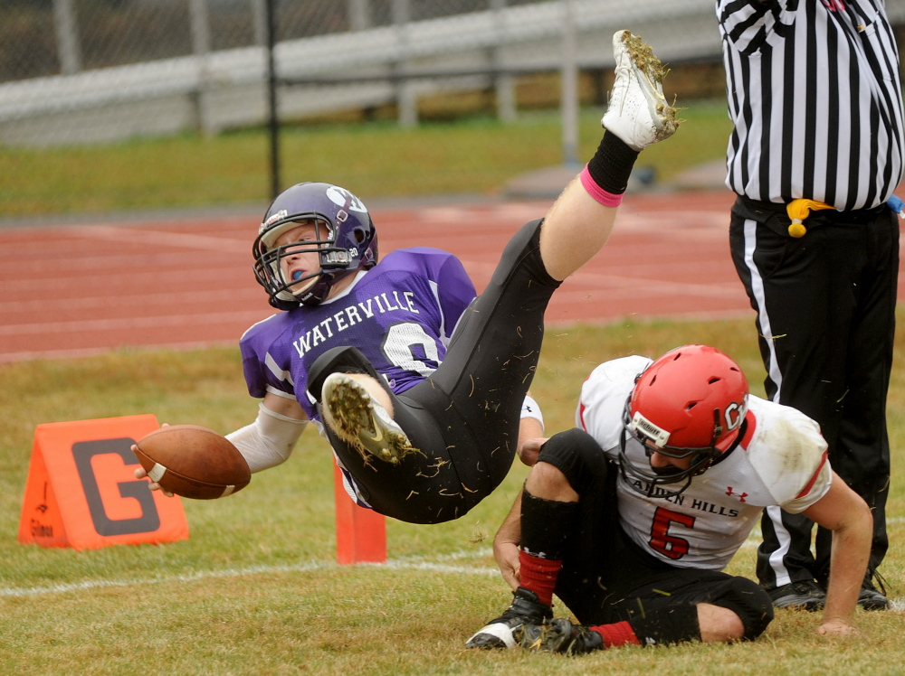 Waterville Senior High School's Daniel Pooler (20) dives over Camden Hills High School defender Ossian Wienges (6) for the touchdown Saturday in Waterville. Waterville defeated Camden Hills 61-14. While Waterville and Winslow have the top two spots locked up for the Eastern Class C playoffs, a group of teams are fighting for spots 3-6.