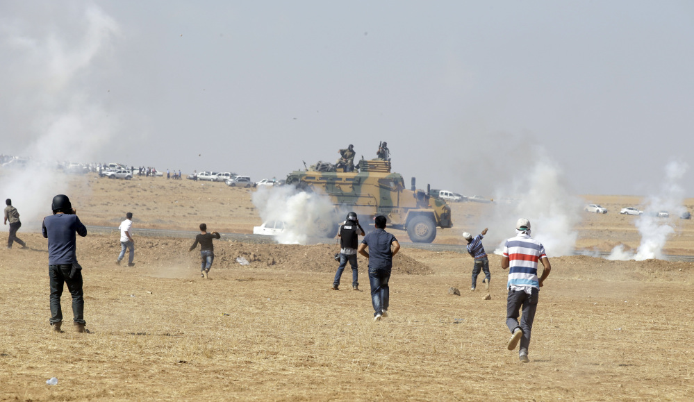 Turkish Kurds in the outskirts of Suruc, at the Turkey-Syria border, run to throw stones towards a Turkish forces armoured vehicle firing tear gas to disperse them after they gathered as fighting intensified between Syrian Kurds and the militants of Islamic State group, in nearby Kobani, Syria, Tuesday.