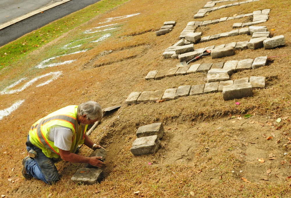 """City worker Andy Chavarie sets a granite cobblestone to make a giant letter E in the """"Welcome to Augusta"""" message that's on Rines Hill, south of downtown Augusta."""