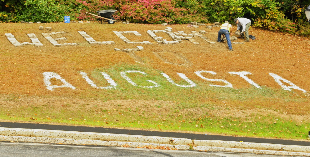 """City workers Andy Chavarie, left, and Robert O'Connor set a granite cobblestones in place Tuesday for the giant letter E in the """"Welcome to Augusta"""" message that's on Rines Hill, south of downtown Augusta. The cobblestones were salvaged during the recent renovation of Market Square."""