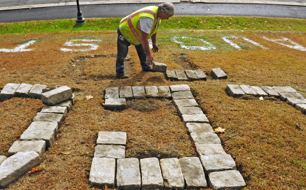 """City worker Andy Chavarie drops a granite cobblestone on Tuesday beside a giant T in the """"Welcome to Augusta"""" message that's on Rines Hill, south of downtown Augusta."""
