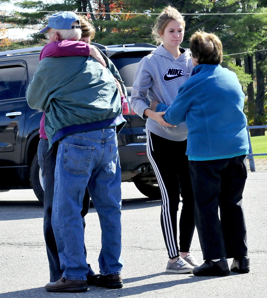 People console each other outside Messalonskee High School in Oakland on Sunday after a gathering of Messalonskee girls soccer team members. Teammate Cassidy Charette died in a hayride accident Saturday in Mechanic Falls.