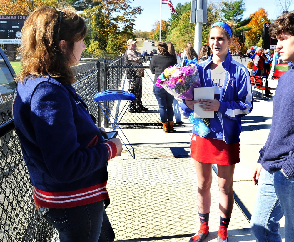 Messalonskee field hockey player Emily Hogan receives flowers and hugs from teammates and players from Skowhegan following a game in Waterville on Monday. She is speaking with her mother Louise and both said they were grateful for all the support from the school and community after the hayride accident that Emily and others were injured in last weekend. Student Cassidy Charette died in the accident.