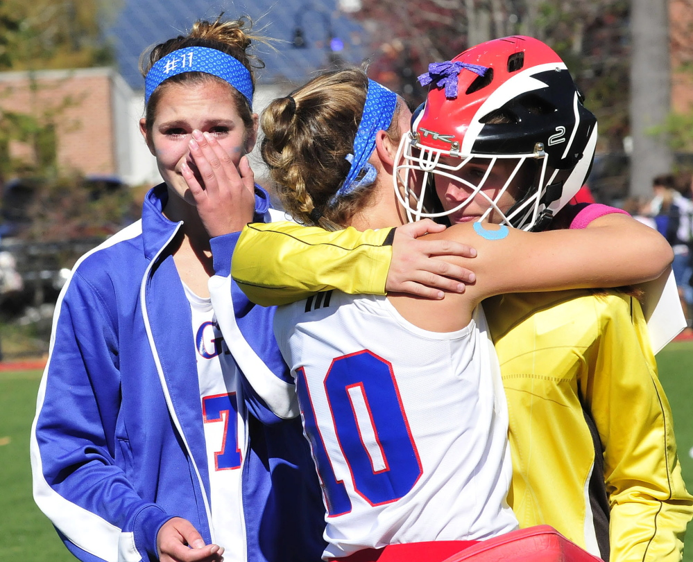 Messalonskee field hockey player Emily Hogan, left, becomes emotional following a game against Skowhegan in Waterville on Monday. Hogan was among 22 people who were injured in a hayride accident on Saturday. Fellow student Cassidy Charette died in the accident. Hogan said she sat out the game but wanted to support the team. She said she has bruises and is sore.