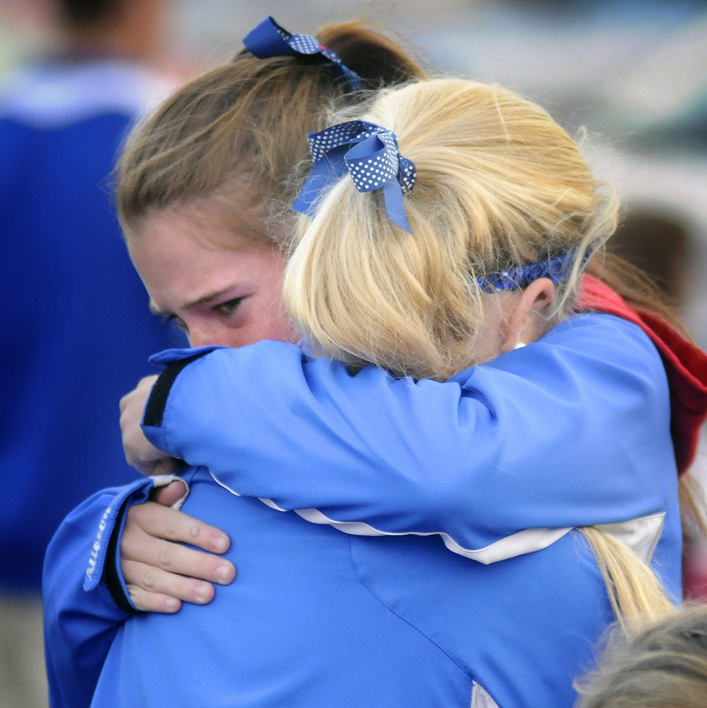 Messalonskee High School soccer players console each other Monday during a fundraiser for the Class of 2016 in Augusta. Their teammate, 17-year-old Cassidy Charette, was killed and her boyfriend, 16-year-old Connor Garland, was injured in an accident on Saturday.