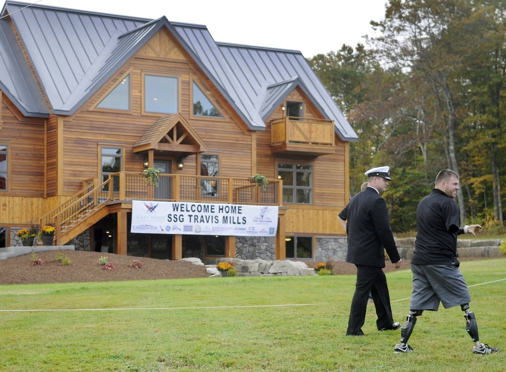 Staff photo by Andy Molloy<br /> Travis Mills walks past his new home Wednesday during a reception in his honor in Manchester. Mills lost all four limbs in an April 2012 explosion while on duty in Afghanistan with the U.S. Army.