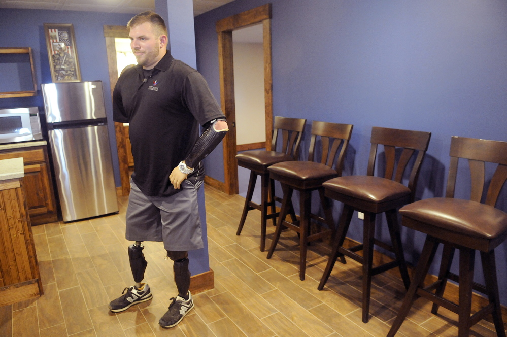 """Staff photo by Andy Molloy<br /> Travis Mills describes the """"man cave"""" in the ground level of his new Manchester home. Mills lost all four limbs in an April 2012 explosion while on duty in Afghanistan with the U.S. Army."""