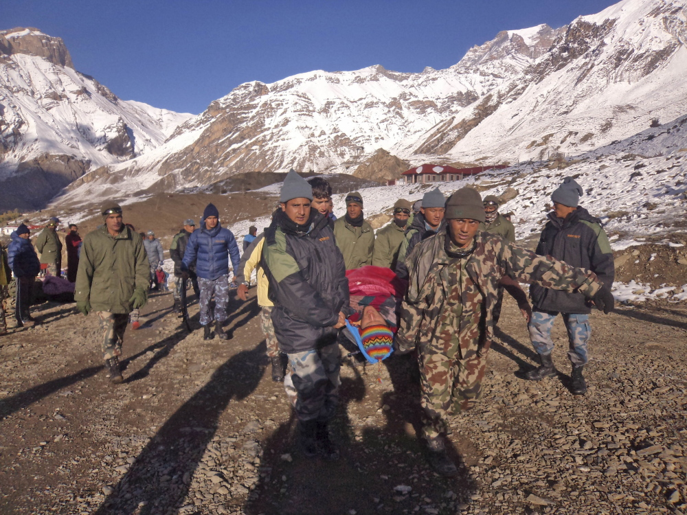 Nepalese army soldiers carry an avalanche victim before he is airlifted in Thorong La pass area, Nepal