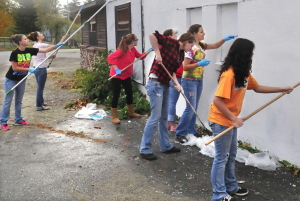 These Carrabec High School seniors and art students paint over a mural at a North Anson building and will eventually paint another mural on it as part of a community service project.