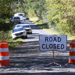 A road closed sign blocks traffic as authorities search a rural area where human remains were discovered in Albermarle County, Va., Sunday.