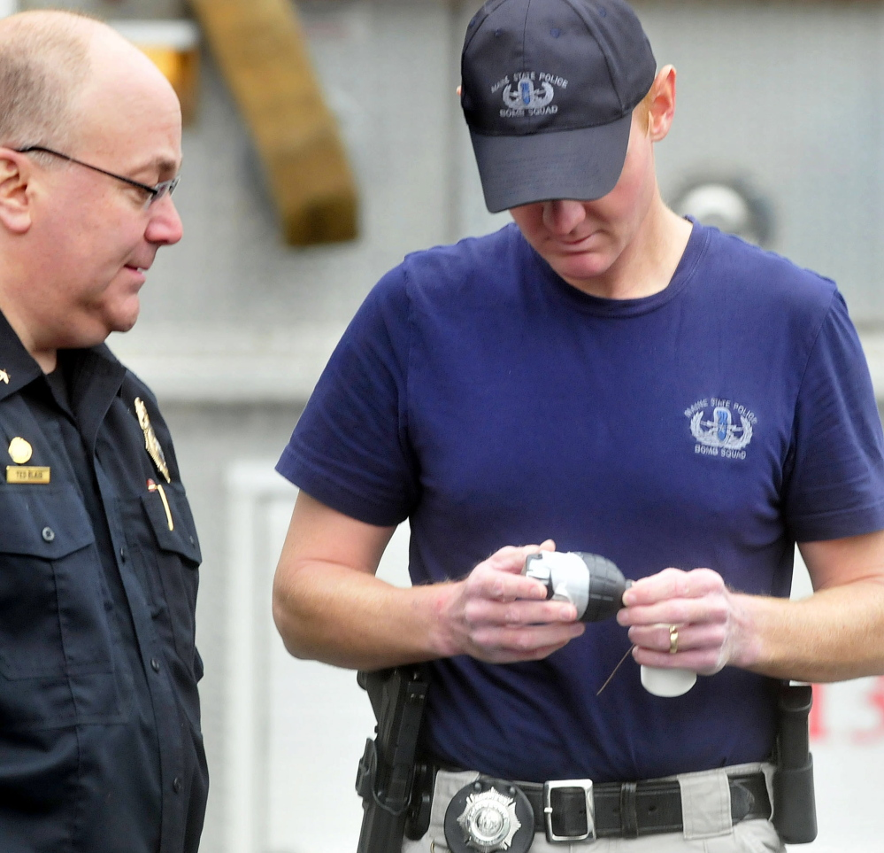 Skowhegan Police Chief Ted Blais, left, looks at a toy held by Trooper Benjamin Sweeney, a member of the state police bomb team, who retrieved the object Tuesday beside the Towne Motel in Skowhegan. The motel was evacuated after an employee discovered the object, which resembles a hand grenade.