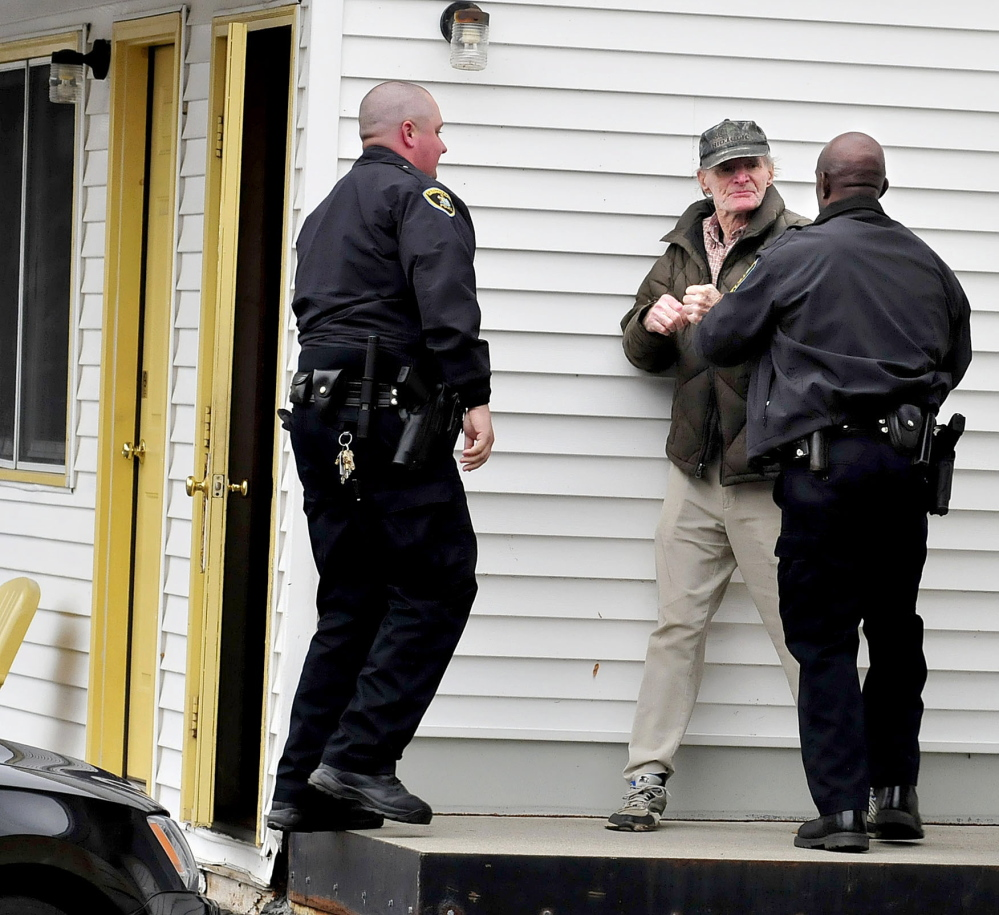 Skowhegan police officers Brian Crater, left, and Tim Williams arrest Robert Schanil after he crossed a cordoned-off area to enter his room Tuesday at the Towne Motel. The motel was evacuated earlier after an object resembling a hand grenade was found nearby.