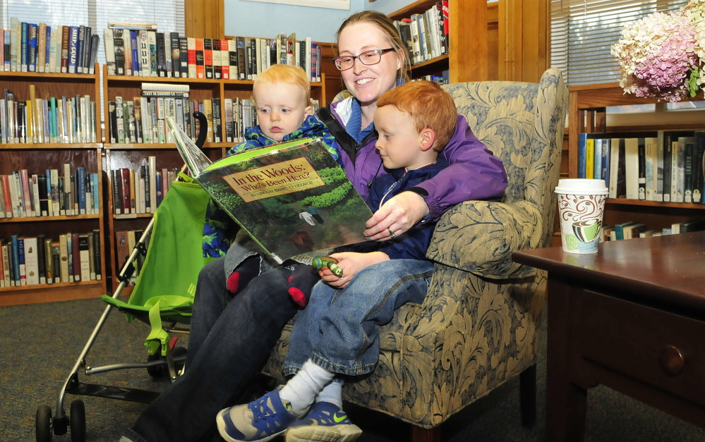 "Kate Whitmore reads to her children Clark, left, and Rory on Tuesday at the Wilton Free Public Library. Whitmore said she thinks the library's decision to start selling coffee is a great idea. ""It should bring more people here and have them stay longer,"" Whitmore said."