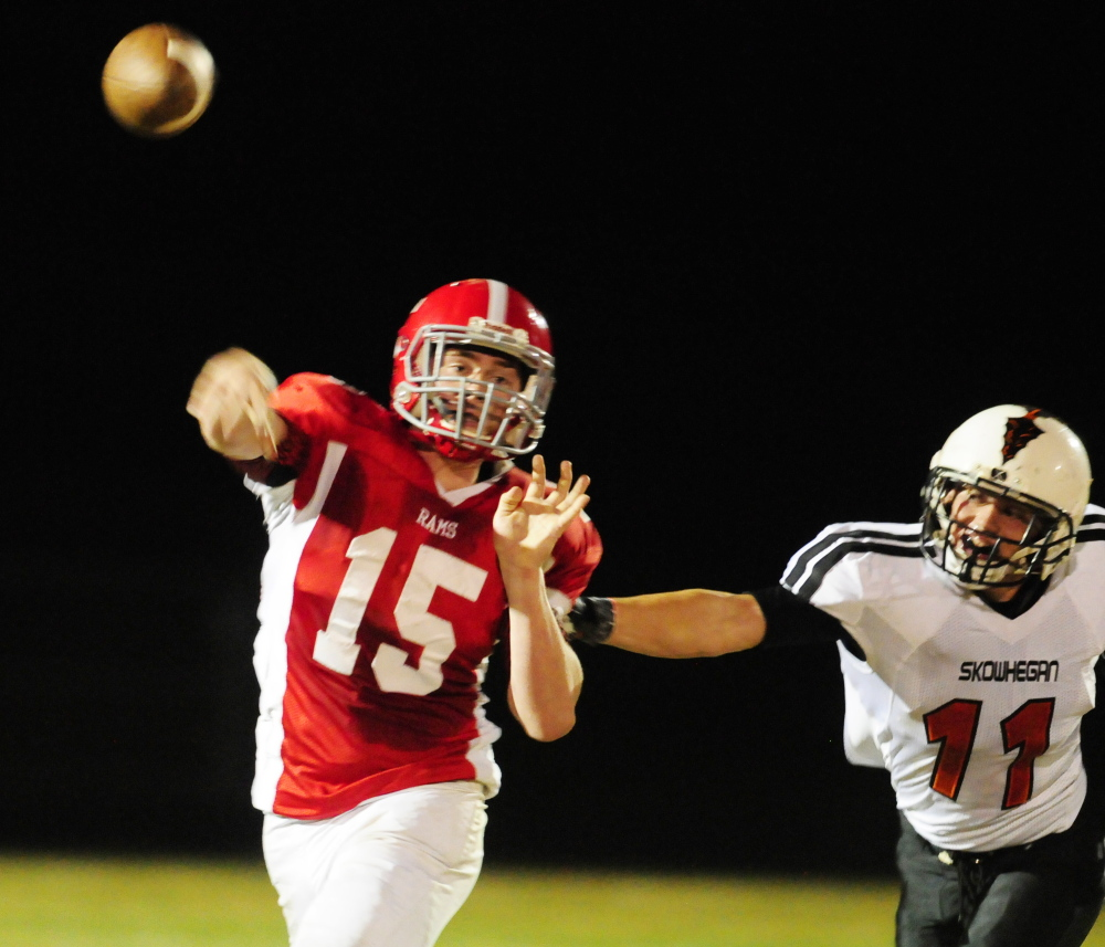 Staff file photo by Joe Phelan   Cony quarterback Mitchell Caron gets a throw off as Skowhegan defensive end Ryan Prentiss grabs him during a Pine Tree Conference Class B game on Oct. 3.