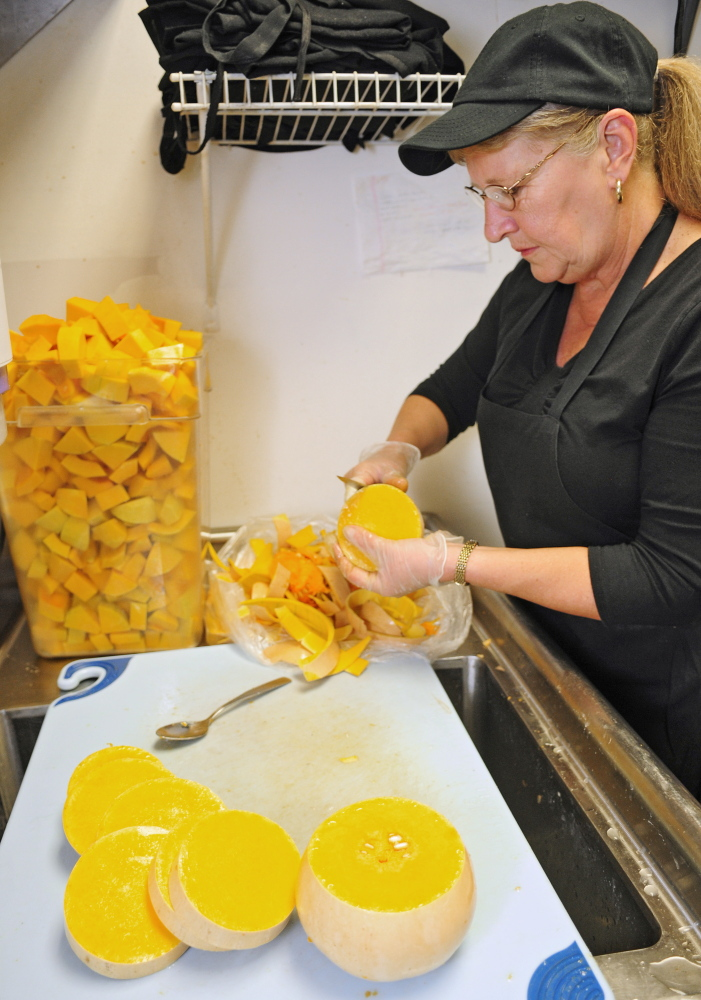 Joe Phelan/Staff Photographer Cohen Center nutrition assistant Priscilla Pushard cuts up butternut squash that was grown by Kennebec County jail inmates.