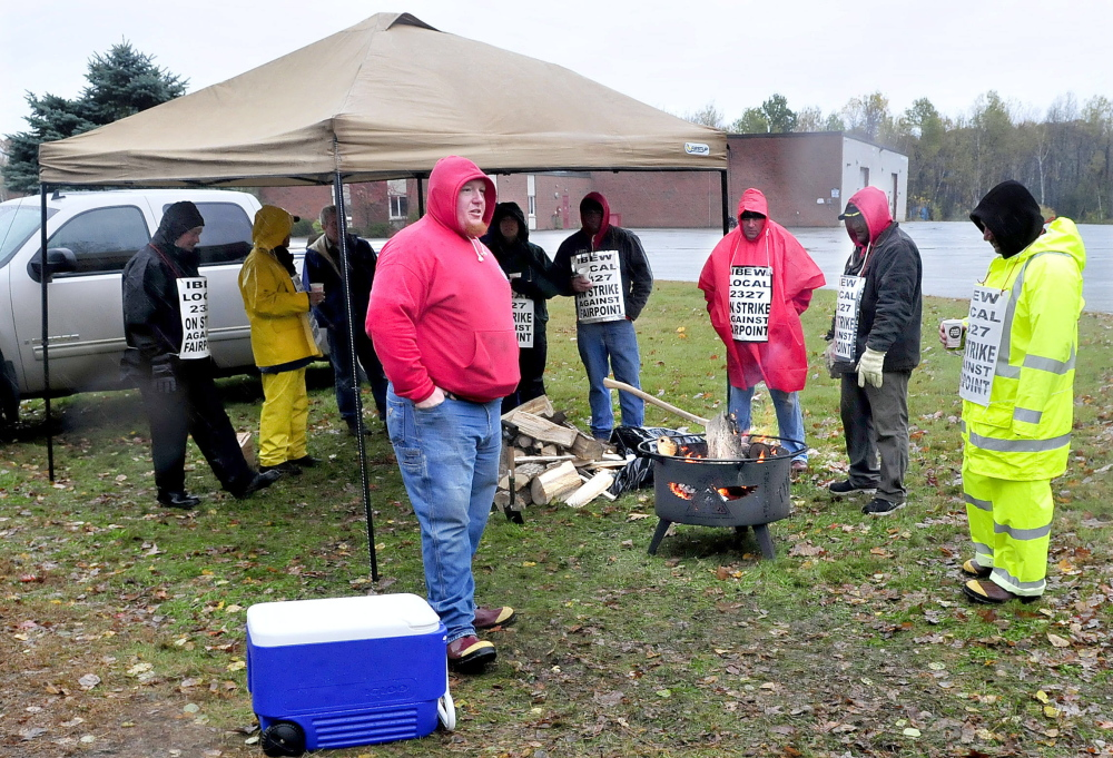 More than a dozen FairPoint employees picket outside the company building in Waterville on Thursday. Todd Foster, center, said the public has shown a lot of support this week by dropping off food, drinks and wood to help the workers stay dry and warm.