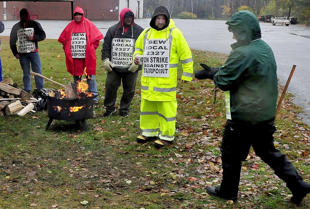 FairPoint company employee Norm Martitz, second from right, greets an employee who arrived to join others picketing outside the company in Waterville on Thursday.