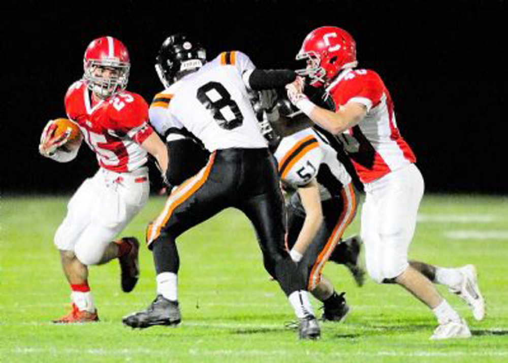 Cony's Tayler Carrier (25) looks for running room as Gardiner's Josh McKelvey (8) and Adrian Heath (51) close in. The teams will play in the 137th meeting between the schools Friday at Hoch Field in Gardiner.