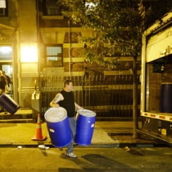 Workers from BioRecoveryCorp carry barrels from the apartment building of Ebola patient Dr. Craig Spencer Friday, Oct. 24, in New York. Spencer remained in stable condition while isolated in a hospital, talking by cellphone to his family and assisting disease detectives who are accounting for his every movement since arriving in New York from Guinea via Europe on Oct. 17.