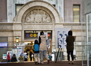 Health alerts for travelers to particular West African countries posted at the main lobby entrance of Bellevue Hospital in New York. New York health officials are known for holdings drills on handling emergencies, and Ebola is no exception. Bellevue, the country's oldest public hospital, had been preparing for an Ebola patient in earnest since August. And when Ebola did come to New York via Dr. Craig Spencer, who had been treating patients in Guinea, he was transported to Bellevue by specially trained emergency workers cloaked in protective gear.