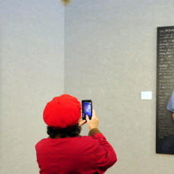 "Sandra Chivington snaps a photo of a portrait Thursday during an opening reception at the Danforth Gallery of ""Reflect: Convicts' Letters to Their Younger Selves,"" at the University of Maine at Augusta."