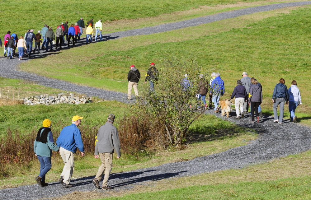 People hike a switchback trail up a hill Saturday during a tour of the new trail between the Maranacook schools and the old Readfield Fairgrounds in Readfield.