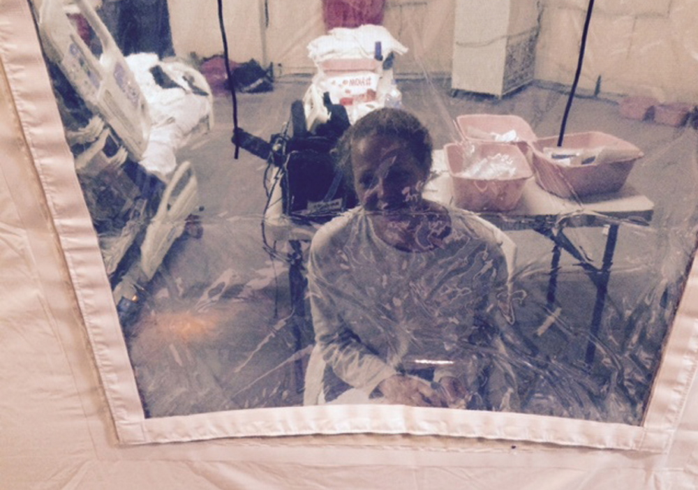 """Nurse Kaci Hickox looks through the plastic """"window"""" of an isolation tent outside a New Jersey hospital where she had been quarantined for days after arriving by plane from West Africa. Hickox, who was free of Ebola symptoms, was released Monday. Photo courtesy of Kaci Hickox attorney Steven Hyman"""