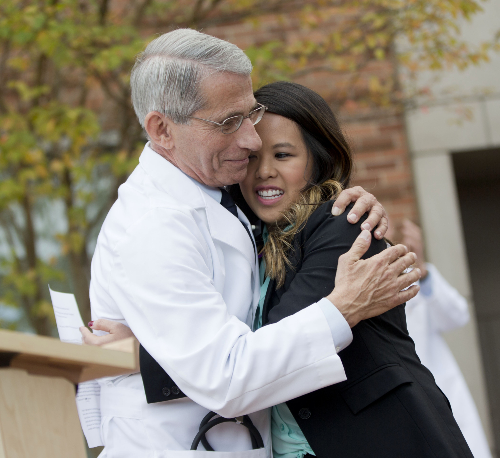 Patient Nina Pham is hugged by Dr. Anthony Fauci, director of the National Institute of Allergy and Infectious Diseases, outside of National Institutes of Health in Bethesda, Md., on Friday. Pham, the first nurse diagnosed with Ebola after treating an infected man at a Dallas hospital, is free of the virus.