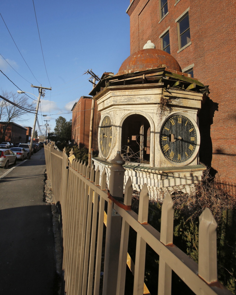 """The clock and roof of the Lincoln Mill clock tower rest on the ground in Biddeford in January 2013. Maine Preservation has named the tower on its annual """"Most Endangered Properties"""" list. Clock towers on mills were used to mark shift changes for workers."""