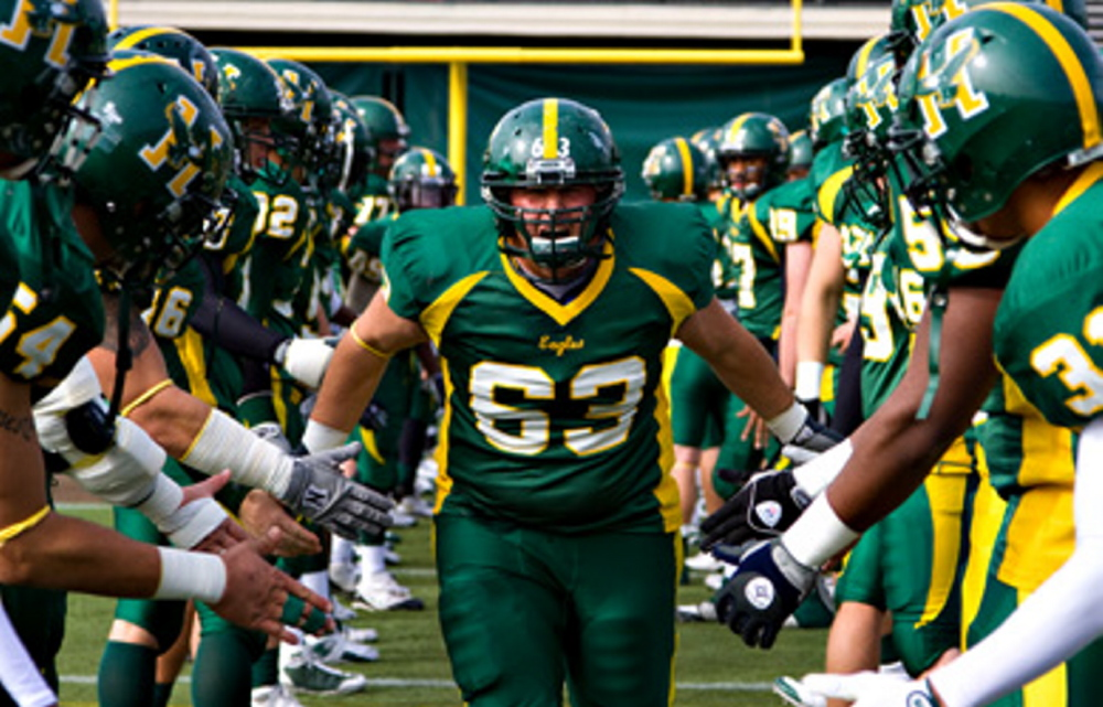 Husson University offensive lineman Matt Archer runs onto the field prior to a game earlier this season. Archer and the Eagles lead the ECFC in offense at 356.7 yards per game, and rushing, 204.8 yards per game.