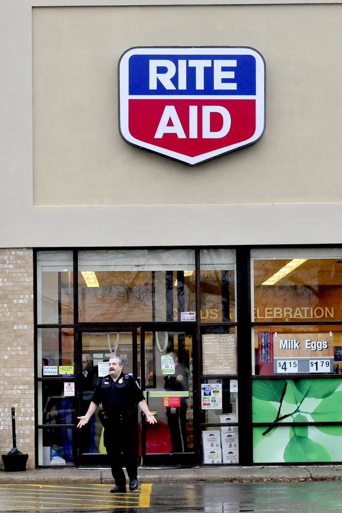 Skowhegan Deputy Police Chief Donald Bolduc instructs pedestrians to leave the parking lot of the Rite Aid store in Skowhegan following a report of a robbery on Wednesday afternoon.