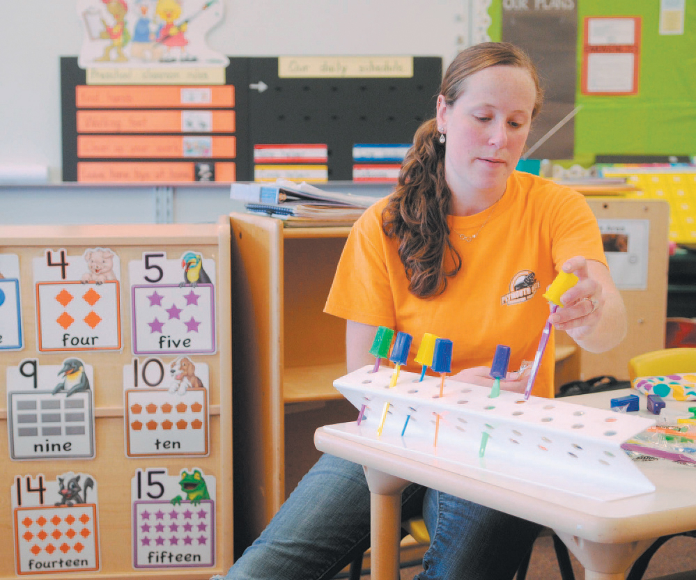 In this 2013 file photo, Windsor Elementary School pre-kindergarten teacher Brittany Hill gets ready at the start of a new school year. Voters in Windsor and Palermo will decide Tuesday whether to withdraw from Regional School Unit 12.