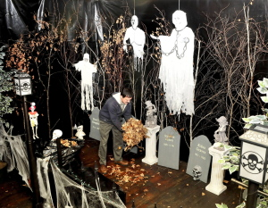Donald Breton spreads leaves on the floor of a cemetery filled with ghosts and skeletons for Halloween at the Old Mill at the former American Woolen mill in Vassalboro. The haunted trail is open 5-8 p.m. Friday