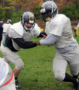 Staff photo by Andy Molloy   Maranacook senior linemen Josh Murphy, left, tags teammate Josh Ehriorobo during practice Wednesday. Murphy is a two-way starter while Ehriorobo is making an impact in his first year on the playoff-bound Black Bears.