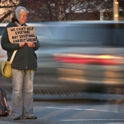 A homeless woman panhandles in Portland. The longterm growth of homelessness in the city has been visible in recent years.