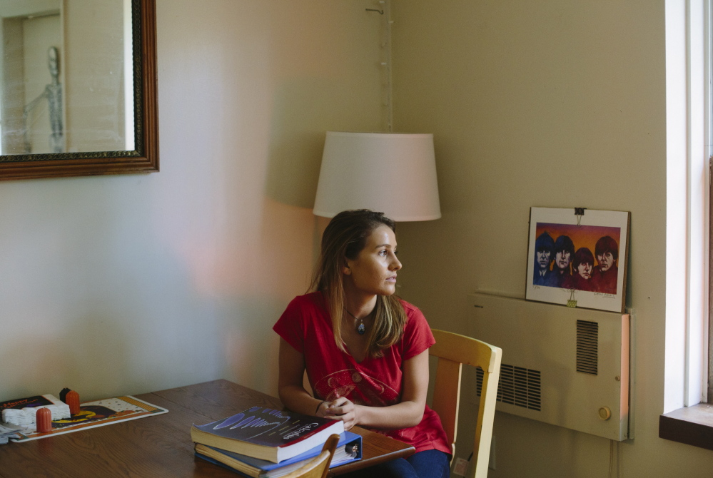 "University of Maine sophomore Olivia Conrad sits in her Orono apartment  last week. Conrad transferred from St. Lawrence University, a private school, after a freshman year that left her $25,000 in debt. ""I'm always thinking about a job. Thinking about paying off that debt,"" she said."
