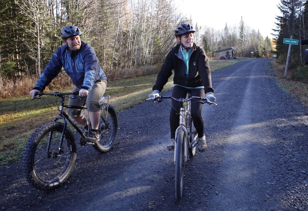 Nurse Kaci Hickox, right, and her boyfriend, Ted Wilbur ride bikes on a trail near her home in Fort Kent, Maine, Thursday, Oct. 30, 2014.  The couple went on an hour-long ride followed by a Maine State Trooper.  State officials are going to court to keep Hickox in quarantine for the remainder of the 21-day incubation period for Ebola that ends on Nov. 10. Police are monitoring her, but can't detain her without a court order signed by a judge.( AP Photo/Robert F. Bukaty)