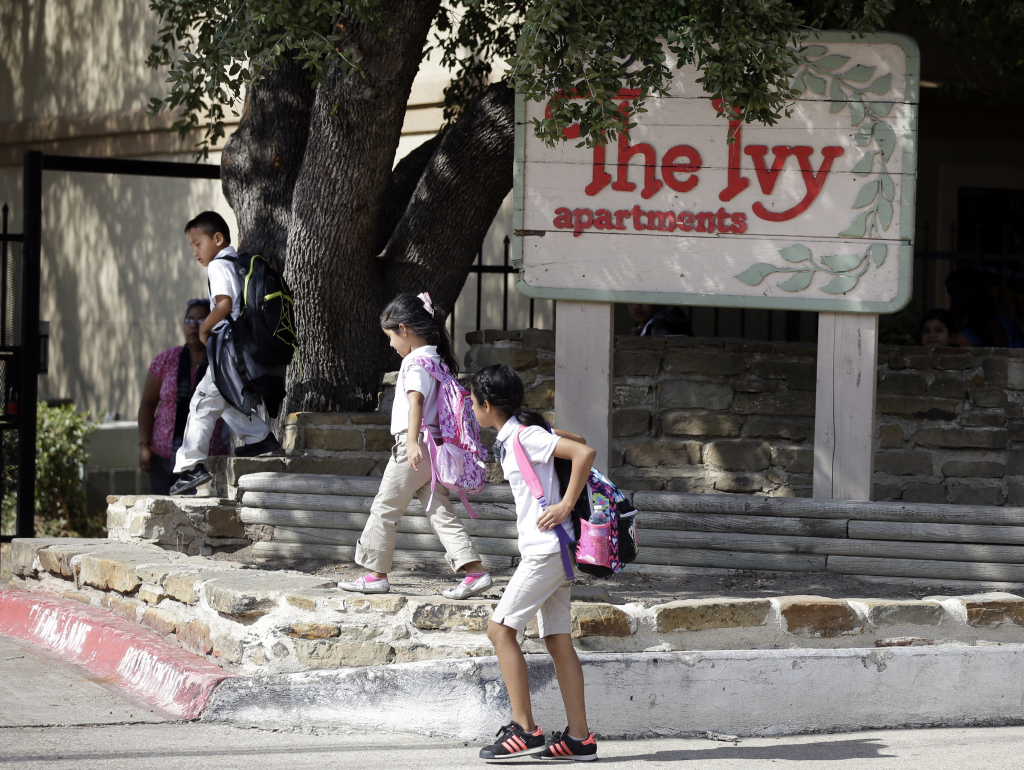 Children arriving home from school walk past the main entrance to The Ivy Apartments complex, Wednesday, in Dallas. The man diagnosed with having the Ebola virus was staying at the complex with family. The Associated Press