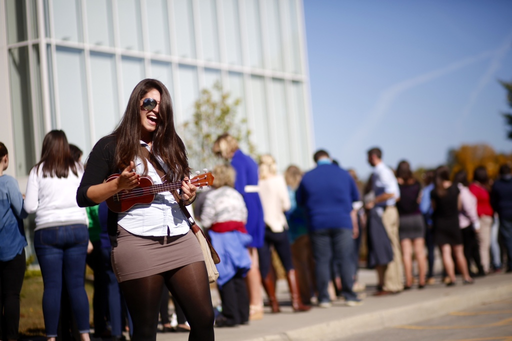 Victoria Mason, a senior at the University of Maine, sings and plays the ukulele as she waits in line outside the Collins Center for the Arts at the University of Maine in Orono to see first lady Michelle Obama speak in support of the Democratic candidate for governor, U.S. Rep. Mike Michaud, on Friday.