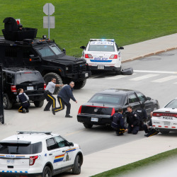 Police officers take cover near Parliament Hilll following a shooting incident in Ottawa on Wednesday.