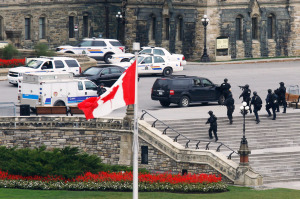 Armed RCMP officers approach Centre Block on Parliament Hilll following a shooting incident in Ottawa on Wednesday.