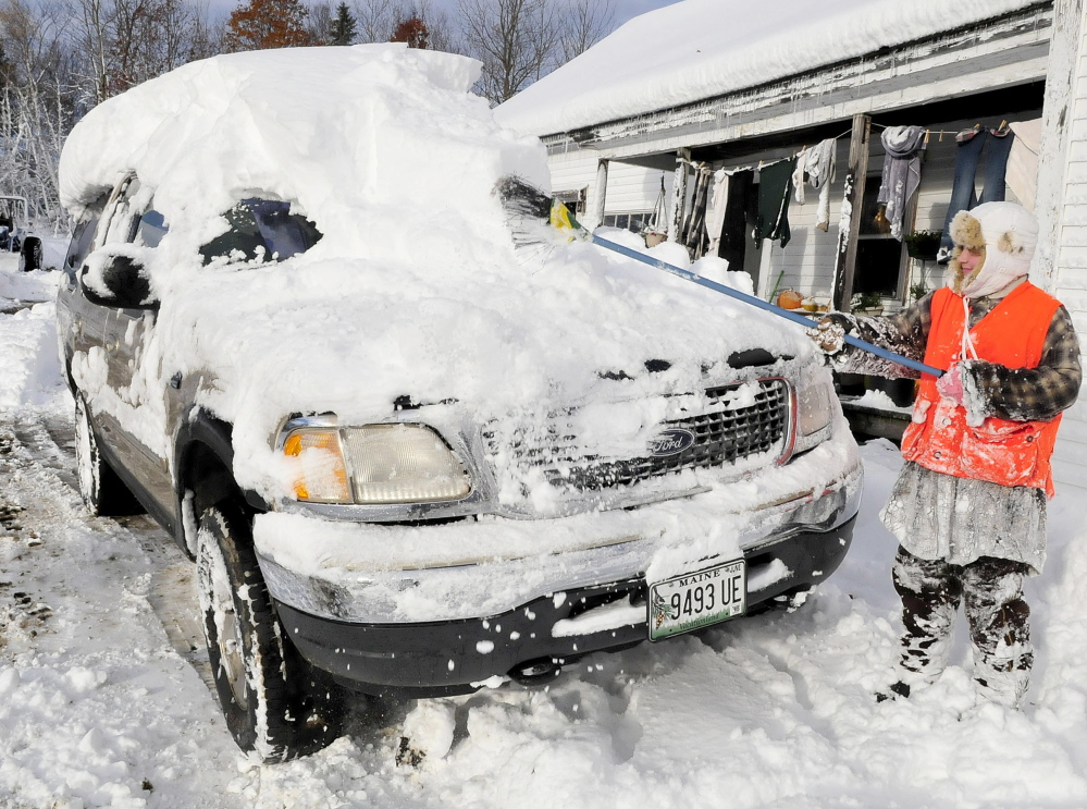 Sydney Astbury uses a broom on Monday to clear the nearly foot of snow that buried the family vehicle at her home in Troy. Many area towns near Troy are without power as wind and heavy snow hit the area on Sunday.