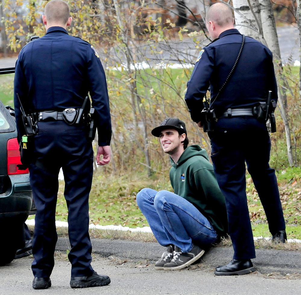 Waterville police officers speak with Joseph Ciampa, handcuffed outside his vehicle on Airport Road in Waterville .