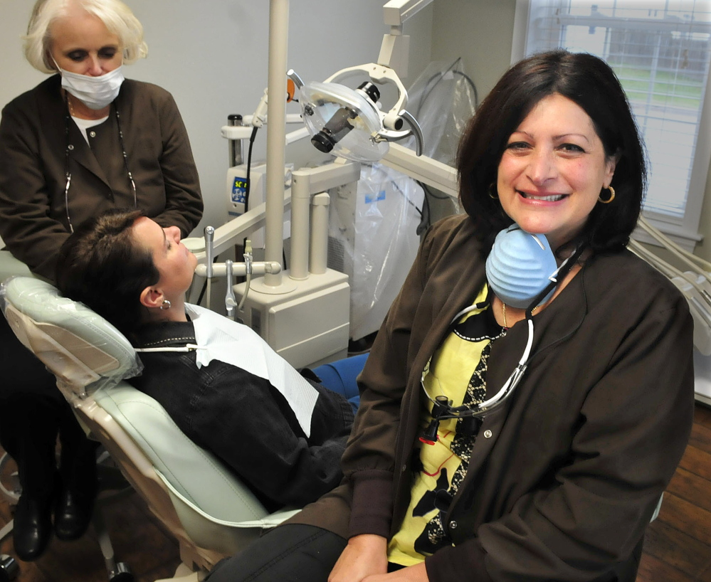 Demi Kouzounas, right, a dentist and co-founder of Dentists Who Care for ME, will offer free dental care Friday to people without insurance at Northwoods Dental in Skowhegan. At left, technician Jayne Hart prepares Denise Bateman for an exam.
