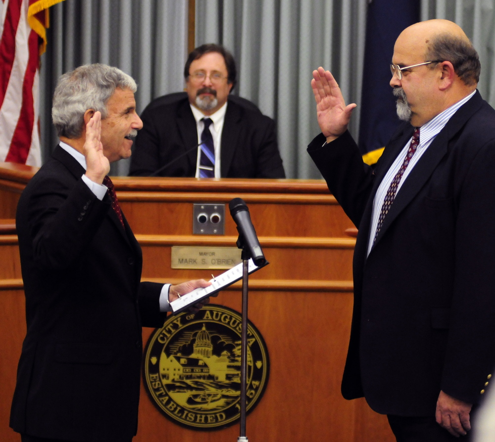 Sen. Roger Katz, left, administers the oath of office Thursday to newly elected Augusta Mayor Dave Rollins at the start of a City Council meeting at Augusta City Center. Outgoing Mayor Mark O'Brien, center, watches the ceremony.