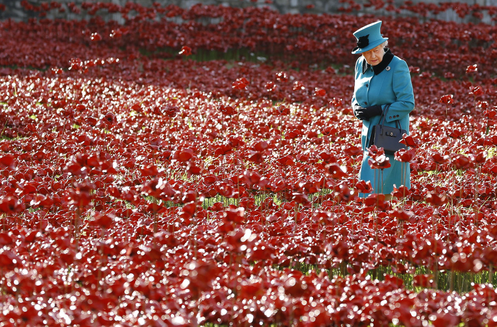 Britain's Queen Elizabeth II walks through a field of ceramic poppies at The Tower of London. This year, the centenary of WWI, the poppy is more ubiquitous than ever.