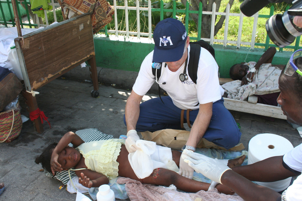 Dr. Robert Fuller provides medical care to an earthquake survivor in Port-au-Prince, Haiti, in January 2010. Three weeks of quarantine imposed on medical professionals who volunteer to go to West Africa to help care for Ebola patients adds to the complications of volunteering. It isn't likely that Fuller will be able to participate if he is required to be away from the University of Connecticut Emergency Medical Department for nine straight weeks.